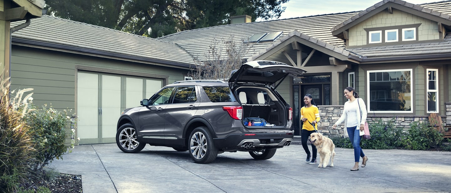 A 2021 Ford Explorer parked in the driveway of a home with a mother and daughter walking their dog toward it