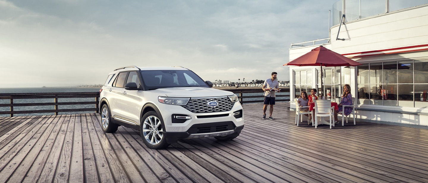 2021 Ford Explorer Platinum in Star White parked on a pier next to a family eating at an outdoor table by a restaurant