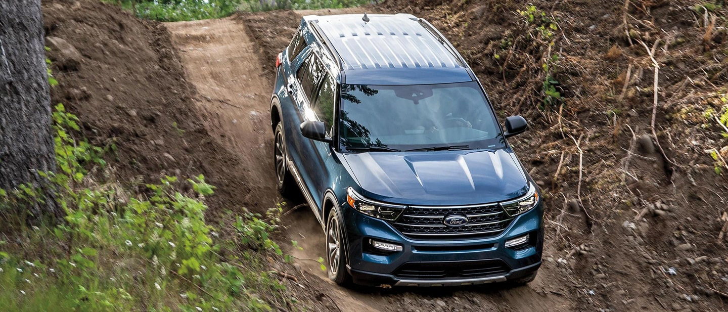 A 2021 Ford Explorer Limited in Blue being driven down a steep dirt hill in a woodsy environment
