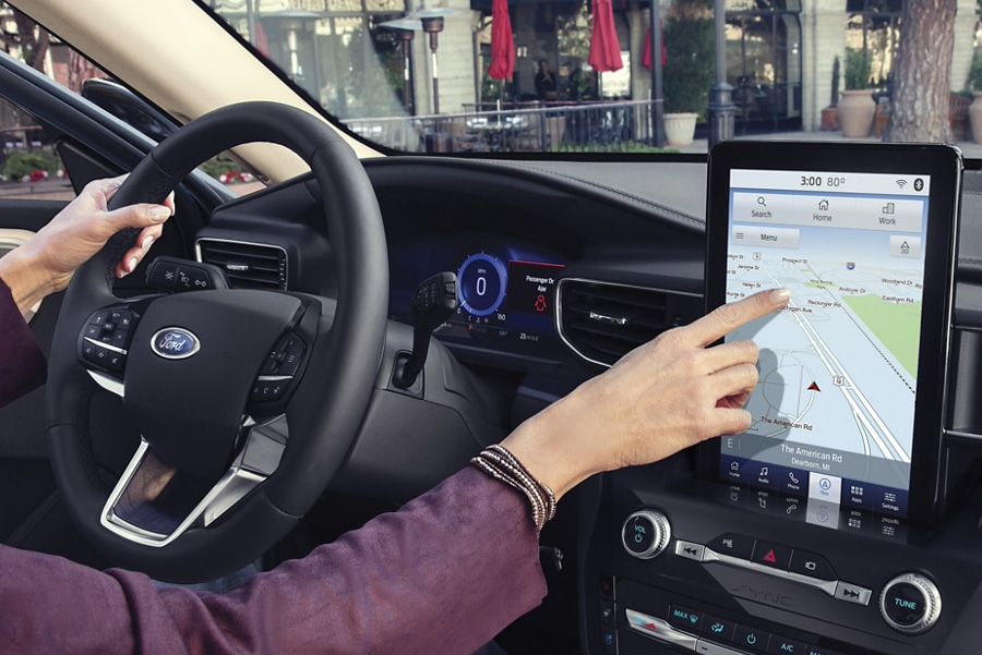 A person in the drivers seat of a 2021 Ford Explorer using the ten point one inch L E D touchscreen