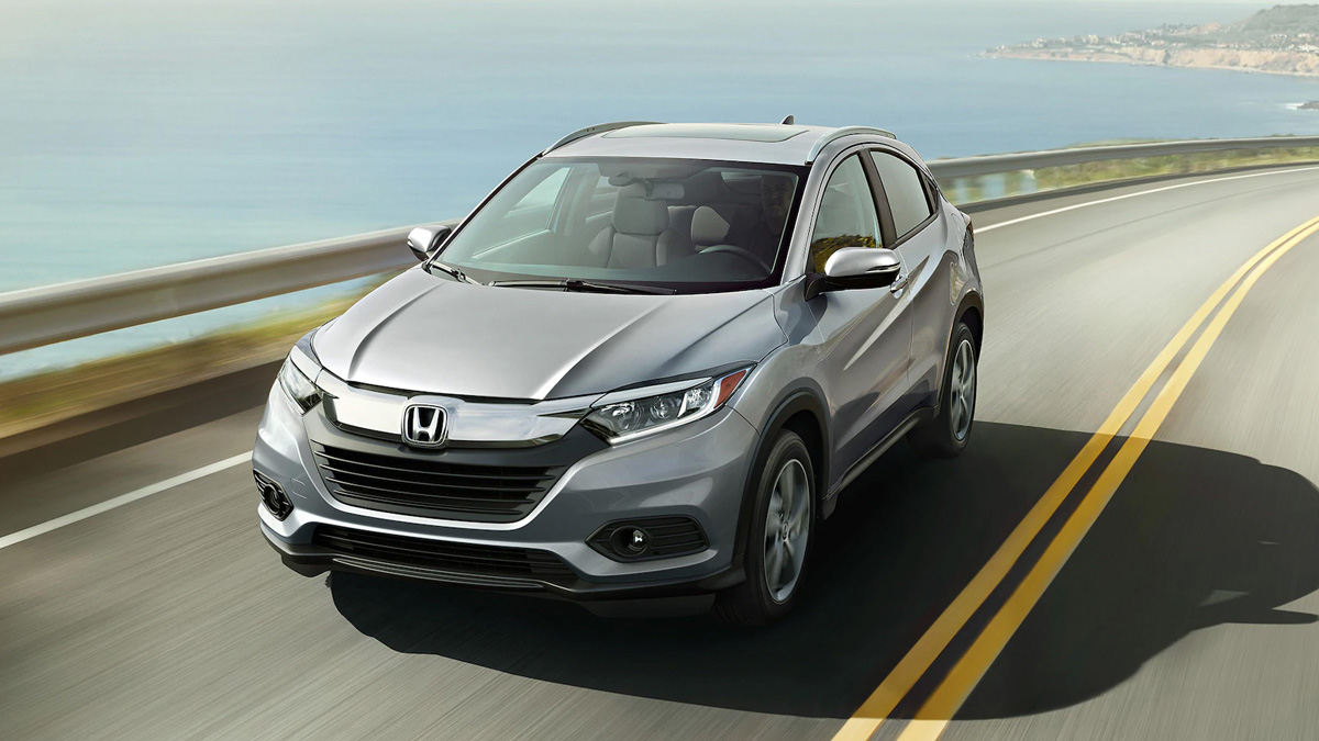 2021 Honda HR-V driving down a road in front of the sea.