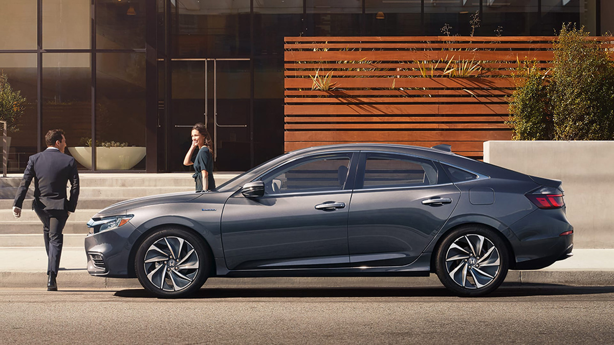 Driver-side profile view of 2021 Honda Insight Touring in Modern Steel Metallic parked in front of modern office building.