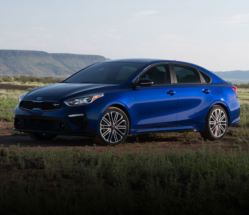 2021 Kia Forte parked in front a mountain range