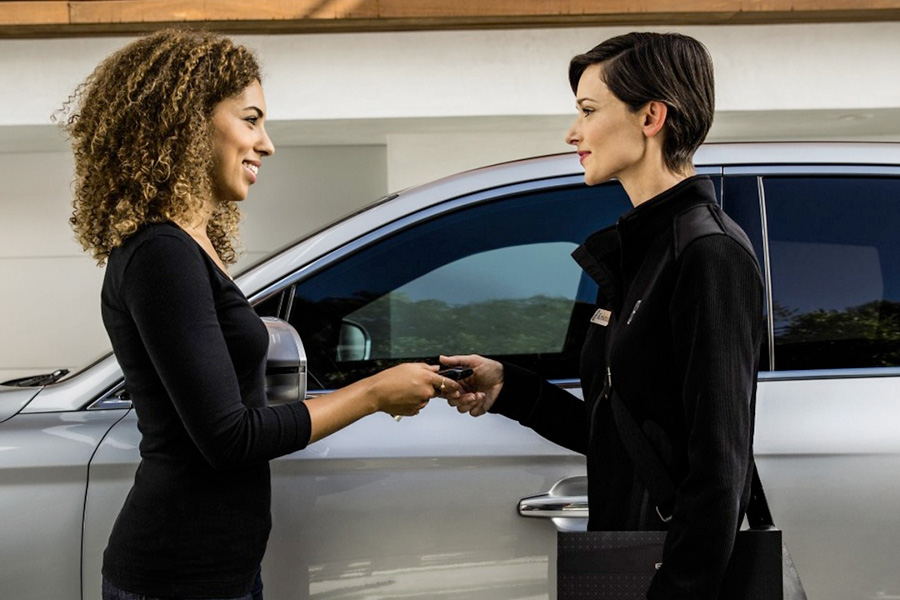 Lincoln sales woman handing keys over to another woman