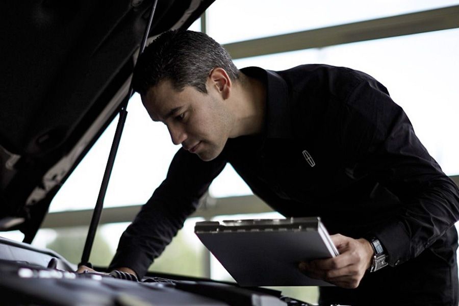 Lincoln service mechanic looking under the hood of a vehicle