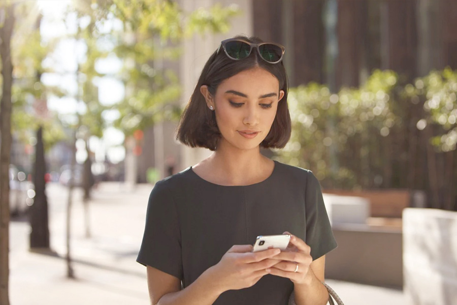 young woman looking at her smartphone while walking
