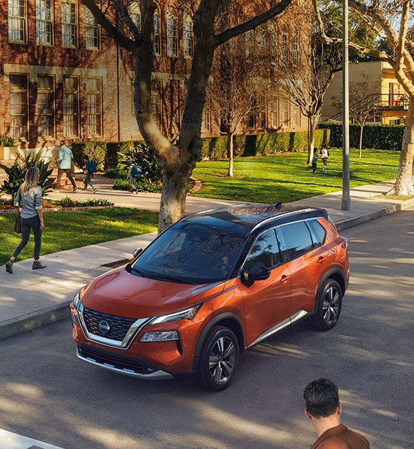 Orange 2021 Nissan Rogue SUV parked outside school