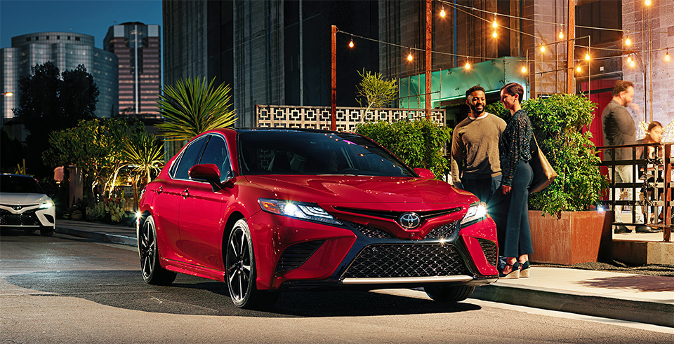 Couple standing next to a Supersonic Red colored 2020 Toyota Camry